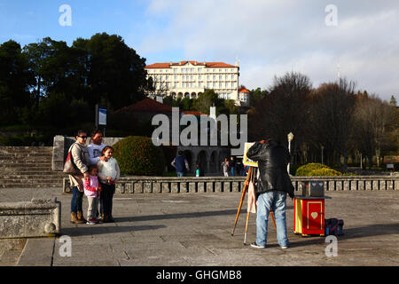 Family have their photo taken on Monte de Santa Luzia, Pousada Santa Luzia hotel behind, Viana do Castelo, northern - Stock Photo