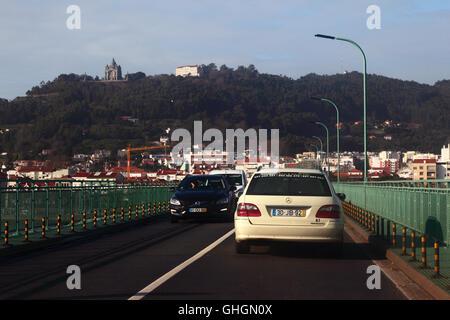Taxi crossing Ponte Eiffel Bridge over River Lima, Santa Luzia basilica in background, Viana do Castelo, northern - Stock Photo