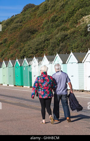 Bournemouth, Dorset, UK. 28 September 2016. Couple walking past shades of green beach huts along promenade of various shades of green with green foliage background on a glorious warm sunny day. Credit:  Carolyn Jenkins/Alamy Live News