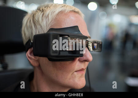 Duesseldorf, Germany. 28th Sep, 2016. A woman wearing the so-called 'Eye Speak' glasses during the opening of the international care fair 'Rheacare' in Duesseldorf, Germany, 28 September 2016. The glasses are equipped with a screen and a virtual keyboard. An inbuild camera recognises the eye movement of the person wearing the glasses, allowing the selection of letters on the monitor. The glasses are said to be a communication system for people with extremely limited movement and communication. The fair runs until 1 October 2016. PHOTO: WOLFRAM KASTL/dpa/Alamy Live News