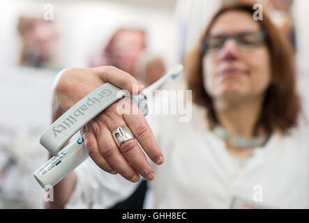 Duesseldorf, Germany. 28th Sep, 2016. A woman holding up a so-called 't.brush' during the opening of the international care fair 'Rheacare' in Duesseldorf, Germany, 28 September 2016. The 't.brush' is a handle for electrical toothbrushes. The fair runs until 1 October 2016. PHOTO: WOLFRAM KASTL/dpa/Alamy Live News