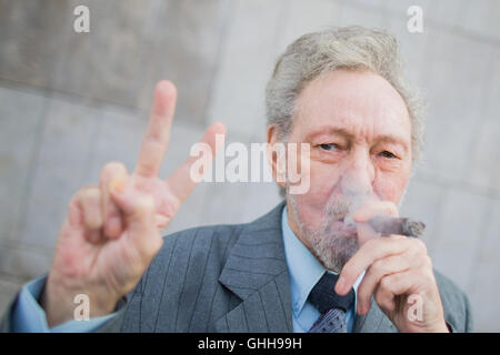 Duesseldorf, Germany. 28th Sep, 2016. Friedhelm Adolfs smokes a cigar and gives the victory sign outside the regional court in Duesseldorf, Germany, 28 September 2016. Adolfs (78) has won an important victory in his legal battle to avoid eviction from his apartment. The regional court in Duesseldorf rejected a lawsuit by his landlady. PHOTO: ROLF VENNENBERND/DPA/Alamy Live News