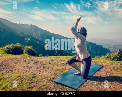 Young woman doing Ashtanga Vinyasa yoga advanced asana - Stock Photo
