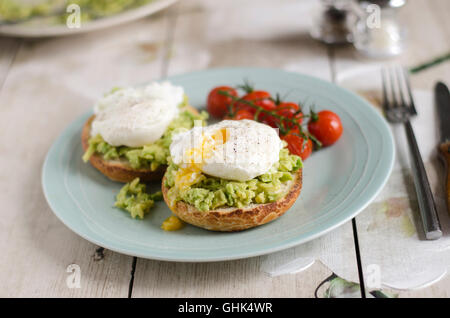 Avocado on toast with poached eggs and tomatoes - Stock Photo