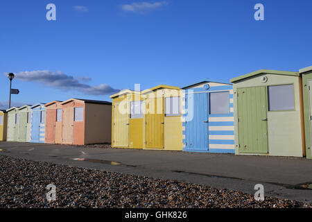 Row of pastel colored beach huts on the beach at Seaford in East Sussex. England. - Stock Photo
