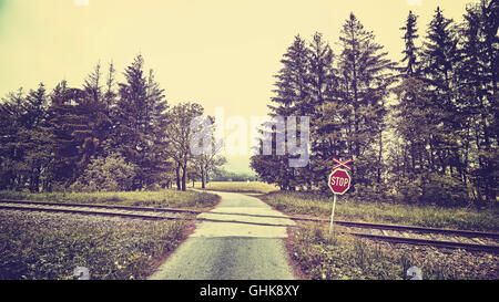 Vintage toned stop sign at railway crossing in a rural landscape. - Stock Photo