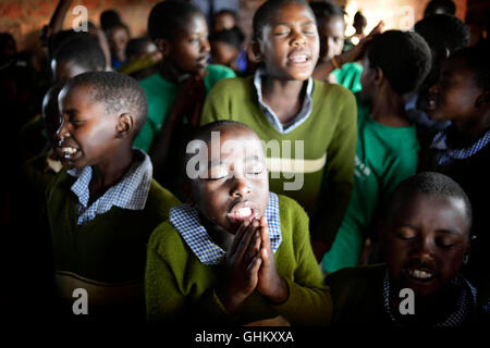 African school children in rural Uganda take a moment during morning assembly to prayer during morning chapel - Stock Photo