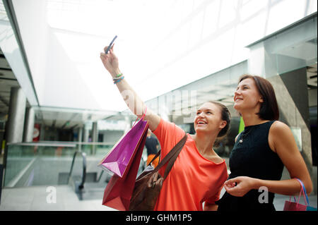 Two cute girls doing selfi at the Mall. In the hands of girlfriends bright packages with purchases. They are posing - Stock Photo