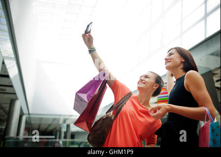 Two cute girlfriends make selfie at the mall. In the hands of one of the girls cell phone. They are posing and laughing. - Stock Photo