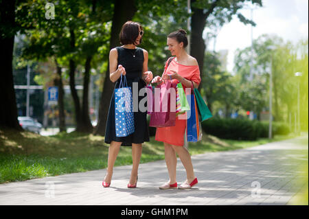 Two girlfriends share their impressions after shopping. Beautiful girls with colorful packages in their hands. They - Stock Photo