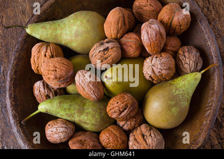 Autumn still life of fall leaves and walnuts on a grunge wooden background - Stock Photo