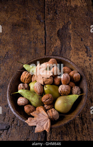 Fall still life with a bowl of pears and walnuts on a grunge wooden background - Stock Photo