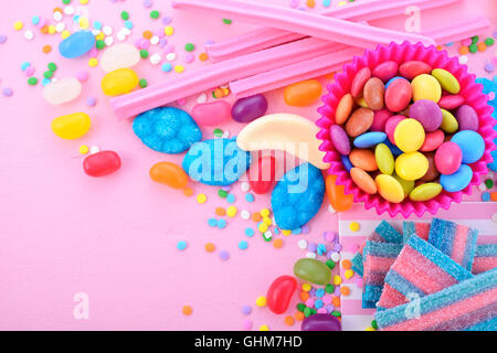 Bright colorful candy background on pink wood table for Halloween trick of treat or childrens birthday party favors, - Stock Photo