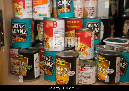 Tins of baked beans on a shelf at North Paddington foodbank waiting collection or distribution - Stock Photo