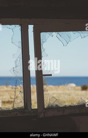View on seacoast through window with broken glass. Decay concept - Stock Photo