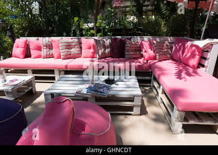 An outdoor garden seating area with a wooden bench and cushions ...