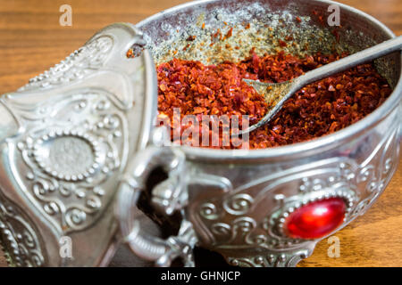 Ground red chili pepper in an ancient silver container with a spoon - Stock Photo
