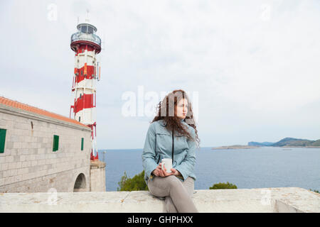Young woman takes a break with lighthouse in background - Stock Photo