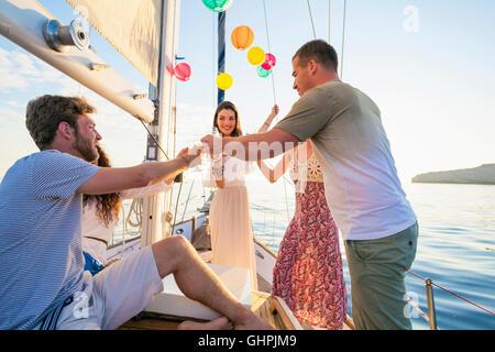Friends toasting wine glasses on sailboat - Stock Photo