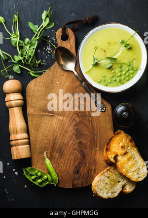 Fresh homemade pea cream soup with bread, copy space - Stock Photo