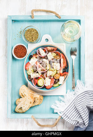 Greek salad with bread, oregano, pepper and glass of wine - Stock Photo