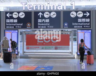People check information at Kansai Airport International Terminal 1 in Osaka Japan. - Stock Photo