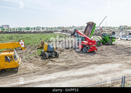 Crane, cherry picker, telescopic forklift and dumper truck are parked in front of building site. - Stock Photo