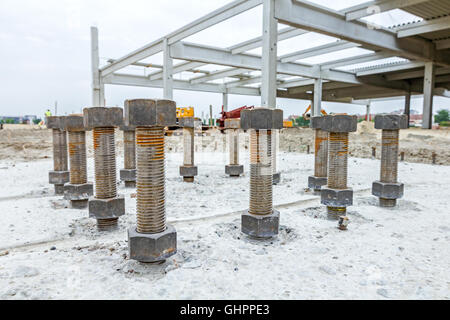 Close up the anchor bolts in concrete base of new edifice with reinforcement at building site. - Stock Photo