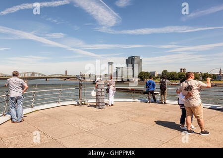 Tourists at the Rhine River promenade with a nice view in the city of Cologne, Germany - Stock Photo