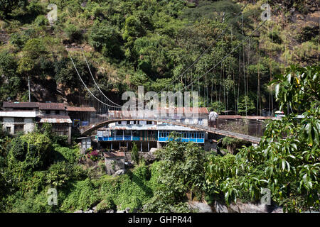 Syange, Nepal - October 24, 2014: A man crossing a suspension bridge over the Marsyangdi River - Stock Photo