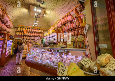 An Italian lady customer is browsing inside of a prosciutto (ham) and cheese shop in Parma, Italy - Stock Photo
