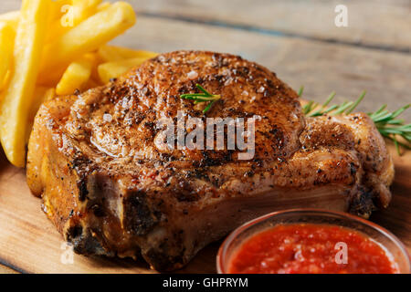steak on the bone steak with french fries and sauce - Stock Photo
