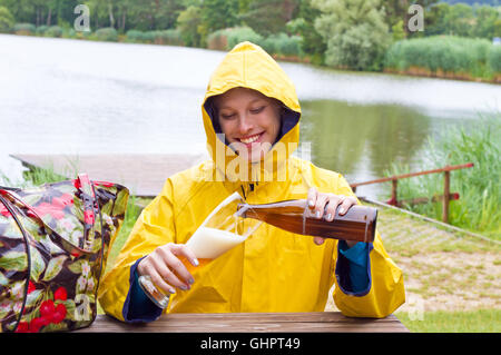 Young, happy woman drinking wheat beer in th rain - Stock Photo