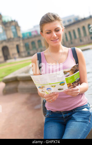 Female tourist reading a travel guide to the Zwinger palace, Dresden, Germany - Stock Photo