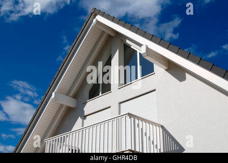 Modern family house building with tiled roof and windows - Stock Photo