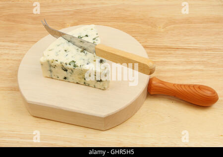 Wedge of Danish blue cheese with a cheese knife on a wooden chopping block - Stock Photo