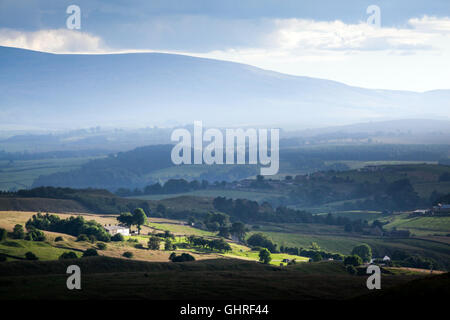 A ray of sunshine catching the farm house and fields with mist rising in the distance in front of the Pennine hills - Stock Photo