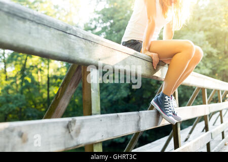 Young woman with beautiful sporty legs sitting on a wooden bridge railing in jeans sneakers - Stock Photo