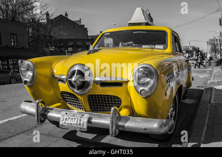 Vintage 1950's Studebaker yellow taxi cab advertising the Caliente Cab in Greenwich Village, New York. Selective - Stock Photo