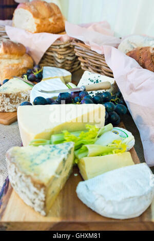 Vertical view of a selection of cheeses on a cheese board with accompaniments. - Stock Photo