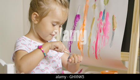 Little girl applying paint to the back of her hand - Stock Photo