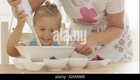 Cute happy little girl helping with the baking - Stock Photo