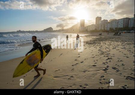 RIO DE JANEIRO - OCTOBER 30, 2015: A Brazilian surfer heads to the sea as a group plays altinho on Copacabana Beach. - Stock Photo