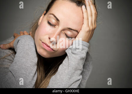 Sad Young woman with eyes closed tears running down face close up hand on head sadness concept - Stock Photo
