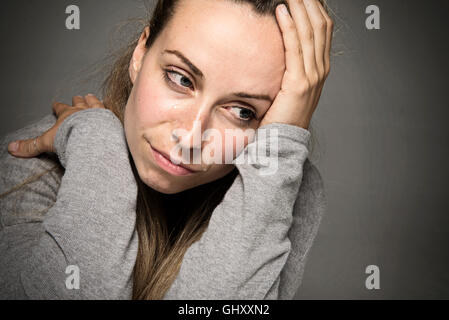 Young sad woman crying with tears running down face close up hand on head sadness concept - Stock Photo