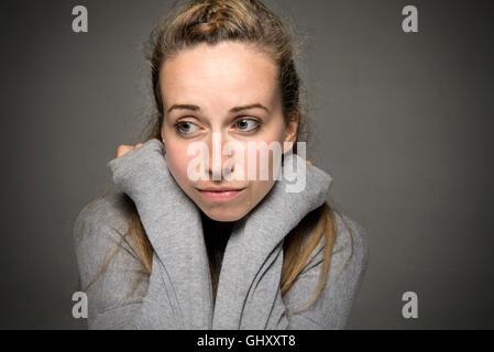 Young woman looking sorrowful with tears running down face hands inside jumper around her neck - Stock Photo