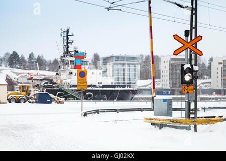 Turky, Finland - January 17, 2016: Railroad crossing near port in snowy winter day - Stock Photo