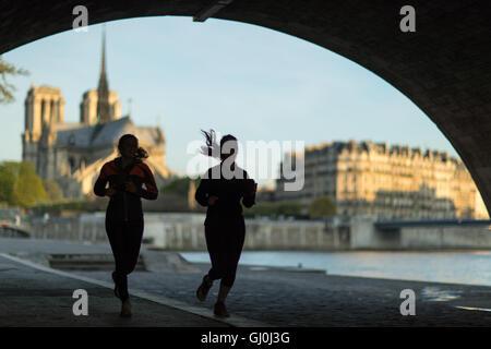 joggers running under the Pont de la Tournelle on the left bank of the River Seine, Paris, France - Stock Photo