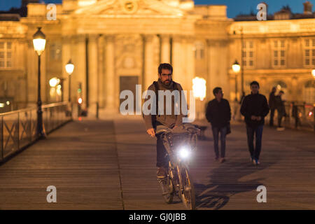 Figures and cyclist on the Pont des Arts at dusk, Paris, France - Stock Photo