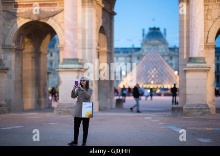 a woman taking a selfie at the Arc de Triomphe du Carrousel & Palais du Louvre at dusk, Paris, France - Stock Photo